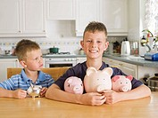 Young Boy Frowning at Boy With More Piggy banks