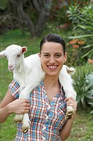 Young girl with goat on shoulders looking into camera happy