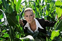 Businesswoman peering through corn