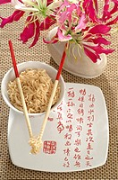 Asian noodles with chopsticks and a flower