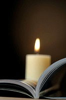 Open book with a candle