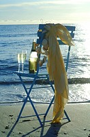 Two glasses of sparkling wine and a bottle on a chair on the beach
