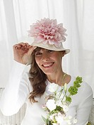Woman wearing a hat with a pink blossom