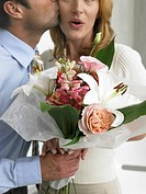 Man kissing woman with a bouquet