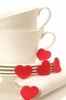 White cups and napkin decorated with red hearts made of felt