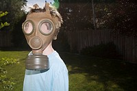 Boy, age 7, wears vintage military gas mask