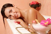 Woman in bath tub with petals