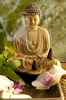 Buddha with incense cone and orchid blossoms