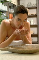 Woman refreshing her face with water from a bowl