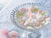 Arrangement of blossoms and swimming candles in a glass bowl