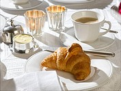 Breakfast table place setting with a croissant