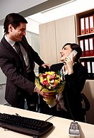 Male office worker giving flowers to female colleague