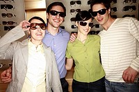 Two couples posing with sunglasses in store