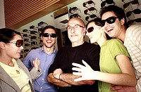 Two couples posing with sunglasses in store with shopkeeper (thumbnail)
