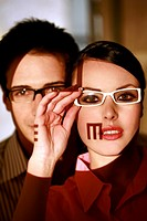 Woman wearing eyeglasses with optical exam characters on her face and man behind