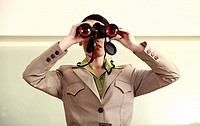 Woman with binoculars standing on counter in eyeglass store