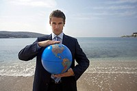 Businessman on beach with globe