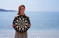 Businesswoman on beach with dartboard (thumbnail)