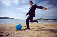 Businessman on beach with globe beach ball (thumbnail)