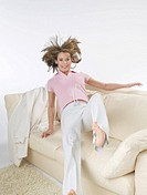 Woman is jumping onto the sofa (thumbnail)