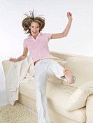 Woman is jumping onto the sofa