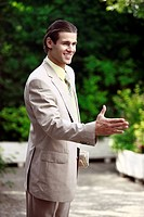 Businessman in garden ready to handshake (thumbnail)