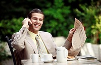 Businessman in garden cafe with cell phone (thumbnail)