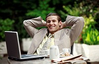 Businessman in garden cafe with laptop