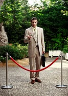 Businessman in garden behind barrier (thumbnail)