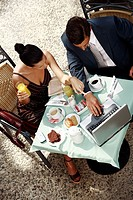 Business couple in garden cafe with laptop
