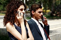 Businessman and businesswoman on cell phones