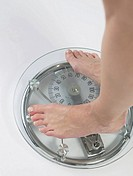 Woman on the bathroom scale, feet