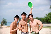 Three men on beach, smiling at camera