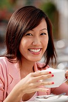 Woman holding coffee cup, smiling at camera