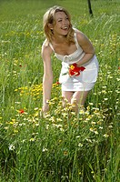 Woman is picking summer flowers in the meadow