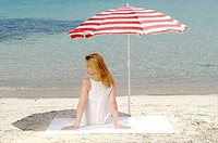 Woman sitting on the beach under a parasol - back view