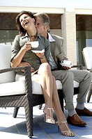 Couple on a bench drinking coffee