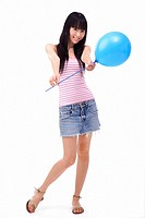 Young woman holding a blue balloon towards camera