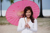 Young woman using pink umbrella
