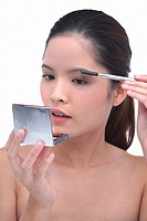 Young woman brushing eyebrows, looking at compact mirror