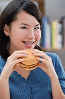 Young woman eating a burger, smiling