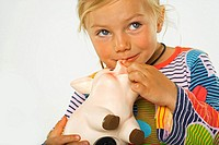 Close-up of a girl holding a piggy bank