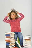 Girl sitting on a stool and holding a book over her head