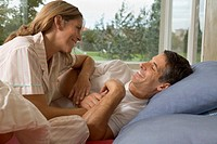 Couple in bed together laughing (thumbnail)