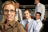 Portrait of a female customer service representative smiling with her four colleagues behind her (thumbnail)