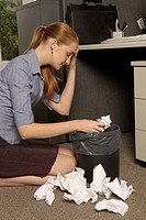 Businesswoman looking in a wastepaper basket