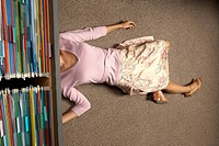 High angle view of a businesswoman lying under a filing cabinet drawer