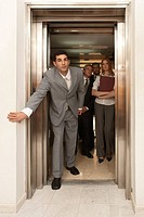 Portrait of a businessman looking outside of an elevator with his colleagues in the background