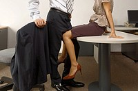 Low section view of a businessman and a businesswoman flirting in an office (thumbnail)