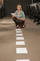 Businesswoman holding a file and crouching in an office in front of a row of papers
